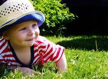Ευτυχές μικρό παιδί στη χλόη Στοκ φωτογραφία με δικαίωμα ελεύθερης χρήσης