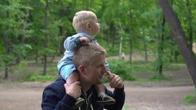 Ευτυχές μικρό παιδί στους ώμους πατέρων ` s στο πάρκο σε αργή κίνηση φιλμ μικρού μήκους