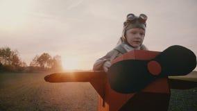 Ευτυχές μικρό παιδί στο κοστούμι αεροπλάνων χαρτονιού διασκέδασης που τρέχει κατά μήκος ενός τομέα φθινοπώρου ηλιοβασιλέματος που απόθεμα βίντεο