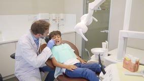 Ευτυχές μικρό παιδί υψηλό fiving ο οδοντίατρός του μετά από την επιτυχή οδοντική εξέταση απόθεμα βίντεο