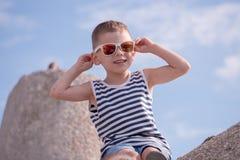 Ευτυχές μικρό παιδί με το μοντέρνο πουκάμισο γυαλιών ηλίου και λωρίδων ναυτικών Στοκ Εικόνες