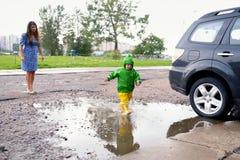 Ευτυχές μικρό παιδί να μην πάρει τα υγρά παιχνίδια ενδυμάτων στη λίμνη στην οδό με τη μητέρα στοκ φωτογραφία