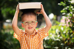 Ευτυχές μικρό παιδί πορτρέτου που κρατά ένα μεγάλο βιβλίο την πρώτη ημέρα του στο σχολείο ή το βρεφικό σταθμό Υπαίθρια, πίσω στη  Στοκ φωτογραφία με δικαίωμα ελεύθερης χρήσης