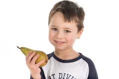 Ευτυχές μικρό παιδί που κρατά ένα αχλάδι Στοκ φωτογραφία με δικαίωμα ελεύθερης χρήσης