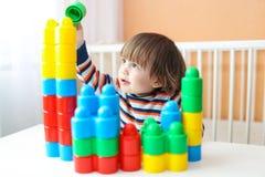 Ευτυχές μικρό παιδί που παίζει τους πλαστικούς φραγμούς Στοκ Φωτογραφίες
