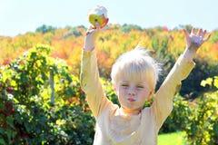 Ευτυχές μικρό παιδί που τρώει τα φρούτα στον οπωρώνα της Apple το φθινόπωρο Στοκ φωτογραφία με δικαίωμα ελεύθερης χρήσης