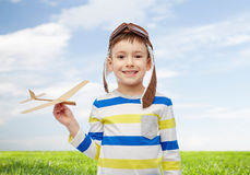 Ευτυχές μικρό παιδί στο καπέλο αεροπόρων με το αεροπλάνο Στοκ εικόνες με δικαίωμα ελεύθερης χρήσης