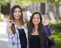 Ευτυχές μικτό ίδιος-φύλο ζεύγος φυλών στη σχολική πανεπιστημιούπολη με το εντάξει σημάδι στοκ εικόνα