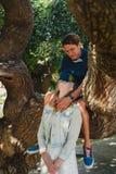 Ευτυχές μοντέρνο αγαπώντας ζεύγος των hipsters που αγκαλιάζει σε ένα πάρκο, συνεδρίαση ατόμων σε ένα δέντρο Στοκ Φωτογραφίες