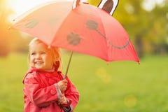 Ευτυχές μωρό με την κόκκινη ομπρέλα Στοκ Φωτογραφία