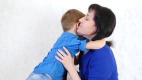 Ευτυχές μωρό που αγκαλιάζει τη συνεδρίαση mom του σε έναν άσπρο καναπέ Η έννοια μιας ευτυχούς οικογένειας απόθεμα βίντεο