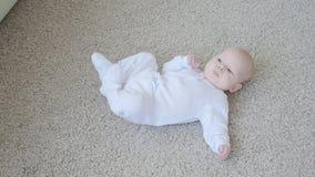 Ευτυχές μωρό που βρίσκεται στο υπόβαθρο ταπήτων, χαμογελώντας κορίτσι παιδιών νηπίων στον άσπρο ιματισμό φιλμ μικρού μήκους