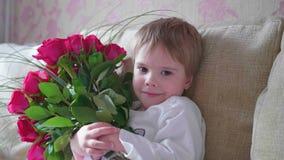 Ευτυχές μωρό που κρατά μια μεγάλη ανθοδέσμη των ερυθρών τριαντάφυλλων Ένα δώρο για τα γενέθλια μητέρων ` s Στοκ Φωτογραφία
