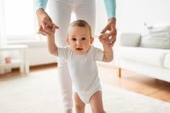 Ευτυχές μωρό που μαθαίνει να περπατά με τη βοήθεια μητέρων Στοκ εικόνα με δικαίωμα ελεύθερης χρήσης