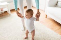 Ευτυχές μωρό που μαθαίνει να περπατά με τη βοήθεια μητέρων Στοκ φωτογραφία με δικαίωμα ελεύθερης χρήσης