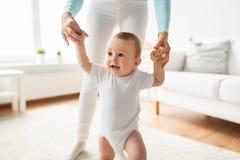 Ευτυχές μωρό που μαθαίνει να περπατά με τη βοήθεια μητέρων Στοκ Εικόνες