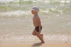 Ευτυχές μωρό που τρέχει από την κυματωγή στην παραλία Στοκ Φωτογραφίες