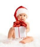 Ευτυχές μωρό σε ένα καπέλο Χριστουγέννων με ένα δώρο που απομονώνεται στοκ φωτογραφίες
