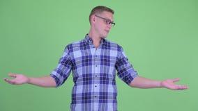 Ευτυχές νέο άτομο hipster που συγκρίνει κάτι φιλμ μικρού μήκους