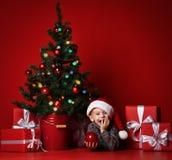 ευτυχές νέο έτος Χριστο&upsilo Πορτρέτο του παιδιού στο κόκκινο καπέλο Santa που περιμένει τα δώρα Χριστουγέννων στοκ εικόνα