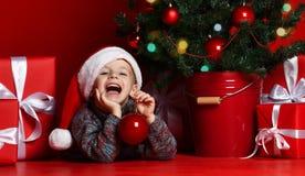 ευτυχές νέο έτος Χριστο&upsilo Πορτρέτο του παιδιού στο κόκκινο καπέλο Santa που περιμένει τα δώρα Χριστουγέννων στοκ εικόνες