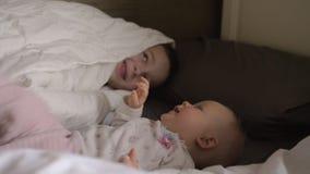 Ευτυχές νέο αγόρι με την αδελφή μωρών του στο κρεβάτι απόθεμα βίντεο