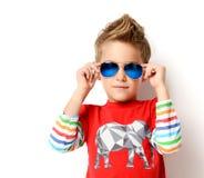 Ευτυχές νέο αγόρι που στέκεται στο ανοικτό κόκκινο πουκάμισο που εξετάζει τη γωνία στα γυαλιά ηλίου στοκ φωτογραφία με δικαίωμα ελεύθερης χρήσης