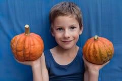 Ευτυχές νέο αγόρι στο μπλε υπόβαθρο με τις κολοκύθες Ζωηρόχρωμες αποκριές ή υγιές σχέδιο τρόπου ζωής στοκ εικόνα με δικαίωμα ελεύθερης χρήσης