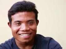 Ευτυχές νέο ασιατικό άτομο που εξετάζει τη φωτογραφική μηχανή Στοκ Εικόνες