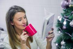 Ευτυχές νέο βιβλίο ανάγνωσης γυναικών μπροστά από το χριστουγεννιάτικο δέντρο στοκ φωτογραφία με δικαίωμα ελεύθερης χρήσης