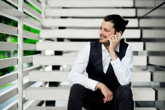 Ευτυχές νέο γενειοφόρο άτομο που μιλά στο κινητά τηλέφωνο και το χαμόγελο Στοκ φωτογραφία με δικαίωμα ελεύθερης χρήσης