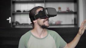 Ευτυχές νέο γενειοφόρο άτομο hipster χρησιμοποιώντας την επίδειξη κασκών VR του για το παιχνίδι εικονικής πραγματικότητας ή προσέ απόθεμα βίντεο