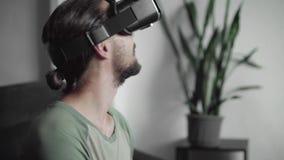 Ευτυχές νέο γενειοφόρο άτομο hipster χρησιμοποιώντας την επίδειξη κασκών VR του για το παιχνίδι εικονικής πραγματικότητας ή προσέ φιλμ μικρού μήκους