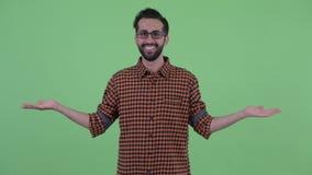 Ευτυχές νέο γενειοφόρο περσικό άτομο hipster που συγκρίνει κάτι φιλμ μικρού μήκους