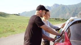 Ευτυχές νέο ζεύγος με έναν χάρτη στο αυτοκίνητο Χρησιμοποιούν το χάρτη στο οδικό ταξίδι απόθεμα βίντεο