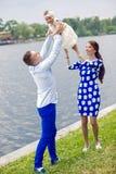 Ευτυχές νέο ζεύγος με τη στάση κοριτσάκι στο νερό Στοκ φωτογραφία με δικαίωμα ελεύθερης χρήσης