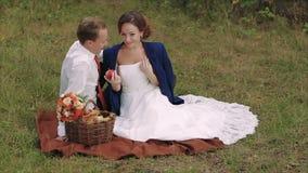 Ευτυχές νέο ζεύγος που έχει το πικ-νίκ στο πάρκο φθινοπώρου απόθεμα βίντεο