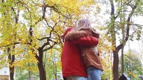 Ευτυχές νέο ζεύγος που αγκαλιάζει στο πάρκο φθινοπώρου φιλμ μικρού μήκους
