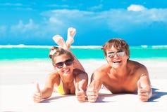 Ευτυχές νέο ζεύγος που βρίσκεται σε μια τροπική παραλία φυλλομετρεί επάνω χειρονομία Στοκ Εικόνα
