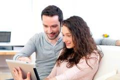 Ευτυχές νέο ζεύγος που κάνει σερφ σε μια ταμπλέτα στοκ εικόνα