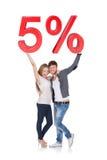 Ευτυχές νέο ζεύγος που κρατά το σημάδι πώλησης 5% Στοκ Φωτογραφία