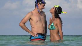 Ευτυχές νέο ζεύγος που κυματίζει στις θερινές διακοπές που κολυμπούν στον ωκεανό απόθεμα βίντεο