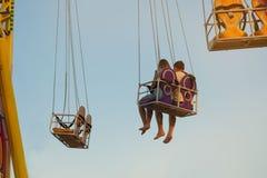 Ευτυχές νέο ζεύγος που οδηγά ένα ιπποδρόμιο σε ένα λούνα παρκ Στοκ εικόνα με δικαίωμα ελεύθερης χρήσης