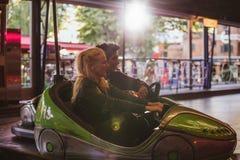 Ευτυχές νέο ζεύγος που οδηγεί ένα αυτοκίνητο προφυλακτήρων στο λούνα παρκ Στοκ Φωτογραφίες