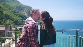 Ευτυχές νέο ζεύγος που στέκεται σε μια γέφυρα παρατήρησης σε ένα υπόβαθρο της παραθεριστικής πόλης κοντά στη θάλασσα και το φιλί απόθεμα βίντεο