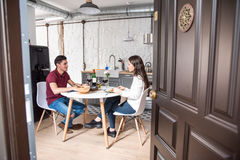 Ευτυχές νέο ζεύγος που τρώει και κρασί κατανάλωσης στο σπίτι Στοκ Εικόνες