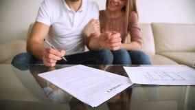 Ευτυχές νέο ζεύγος που υπογράφει το συμφωνητικό σύμβασης και που αγκαλιάζει, επένδυση υποθηκών φιλμ μικρού μήκους