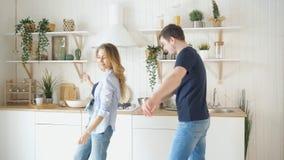 Ευτυχές νέο ζεύγος που χορεύει στην κουζίνα που φορά το χορό τζιν φιλμ μικρού μήκους
