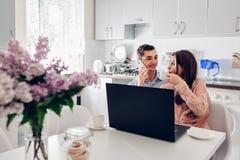 Ευτυχές νέο ζεύγος που χρησιμοποιεί το lap-top ενώ έχοντας το πρόγευμα στη σύγχρονη κουζίνα τηλεφωνικές ομιλούσες &n στοκ εικόνες