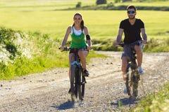 Ευτυχές νέο ζεύγος σε έναν γύρο ποδηλάτων στην επαρχία στοκ εικόνα